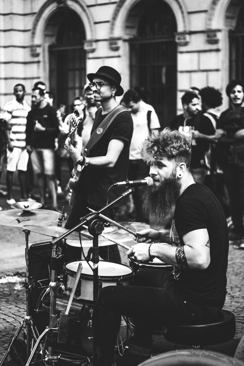 Grayscale Photo of Two Persons Performing Drums and Guitar