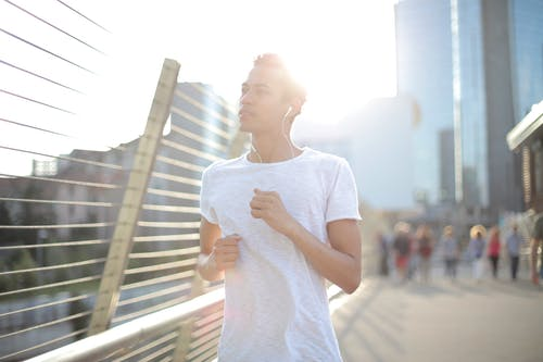 Pensive ethnic runner in earbuds training alone on street in downtown