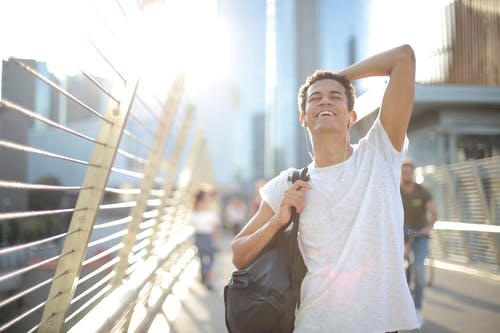 Low angle of overjoyed African American guy in earbuds and casual clothes touching head and laughing while standing with eyes closed on street and listening to music against blurred high rise buildings in downtown