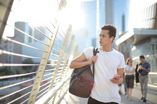 Concentrated guy with smartphone and sportive bag in hands wearing earphones walking on bridge while listening to music