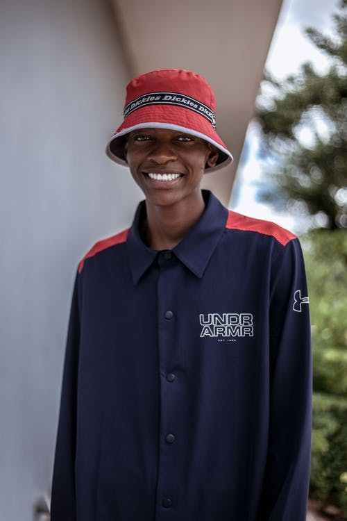Positive African American young male in hat standing near white wall and looking at camera with toothy smile