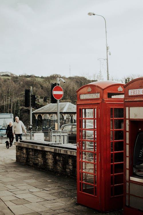 People Walking on Sidewalk Near Red Telephone Booth