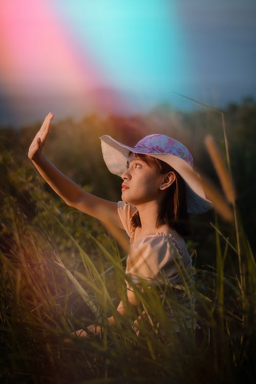 Teen girl sitting in grassy field