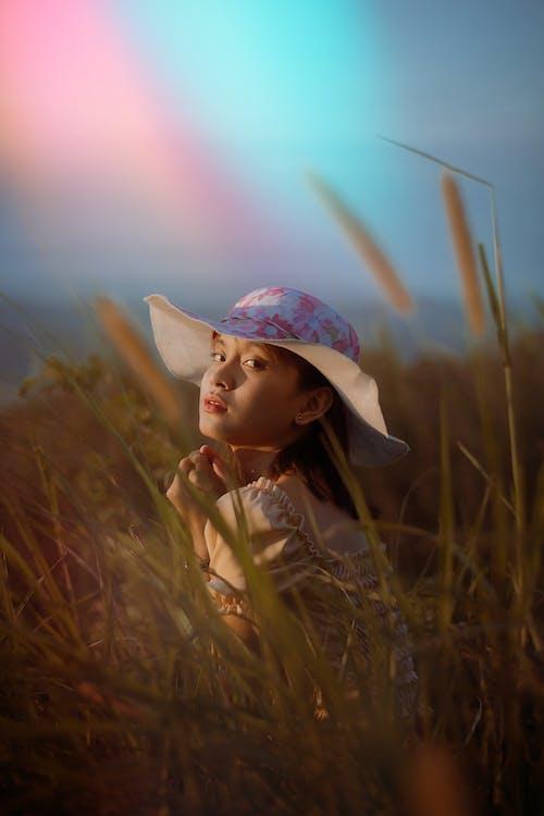 Teen girl enjoying nature in summer day in grassy field