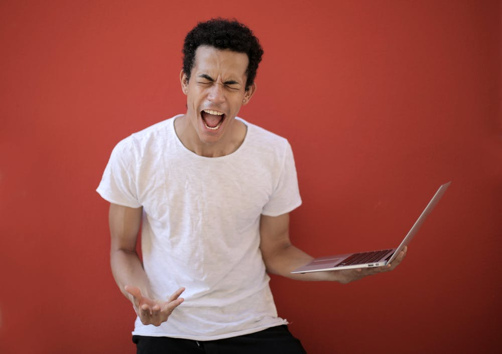 Young man with laptop screaming. | Photo: Getty Images