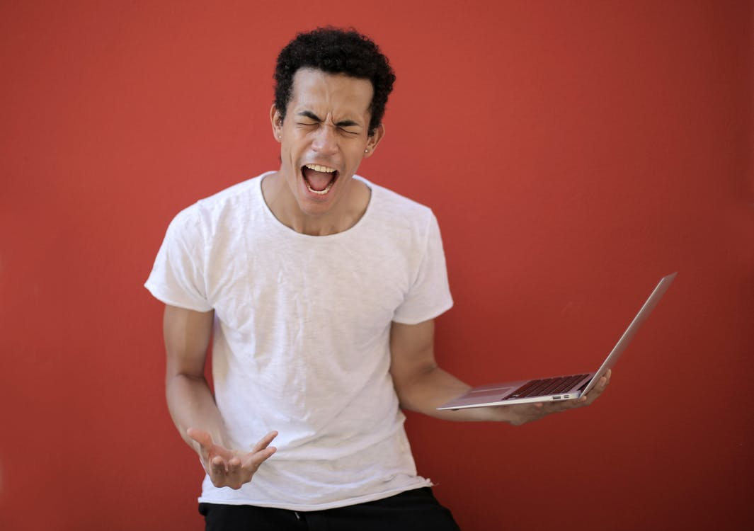 Guy with opened mouth and closed eyes screaming madly while standing with laptop against red background