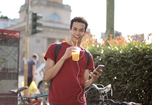 Happy young man using smartphone on street