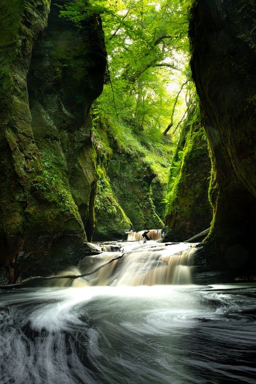 Time-Lapse Photo of River Between Mossy Rocks