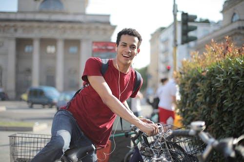 Man Wearing Red Shirt Standing on Bicycle
