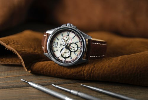 Stylish round wristwatch with chronograph and brown strap placed on leather material near repair tools in modern workshop
