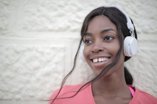 Cheerful black woman listening to music