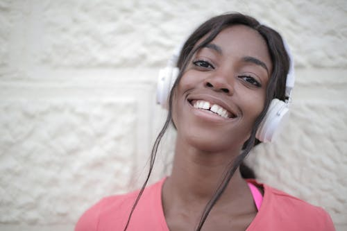 Positive young black female in bright t shirt wearing headphones and listening to music while looking at camera