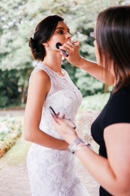Woman Fixing a Bride's Makeup