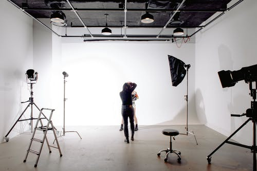 Back view of unrecognizable professional photographer taking photo of anonymous model in modern light studio