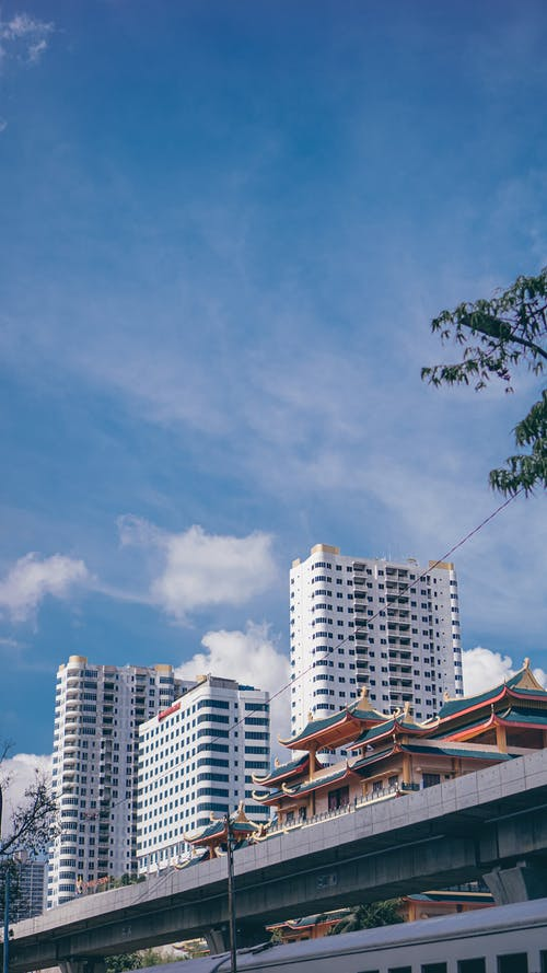 From below of modern city district with tall contemporary buildings near ancient Buddhist temple against blue sky