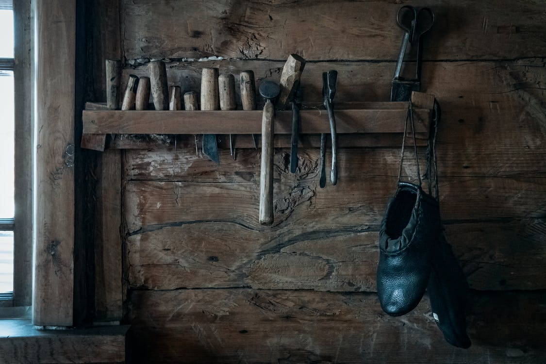 Shoemaker tools hanging on shelf in rustic wooden workshop