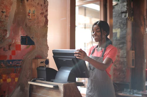 Cheerful American African waitress in apron working on counter monitor while registering order at cozy cafe