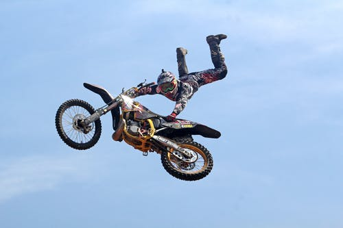 Man Riding Orange Motocross Dirt Bike