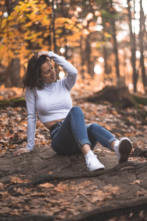Woman in White Long Sleeve Shirt and Blue Denim Jeans Sitting on Ground