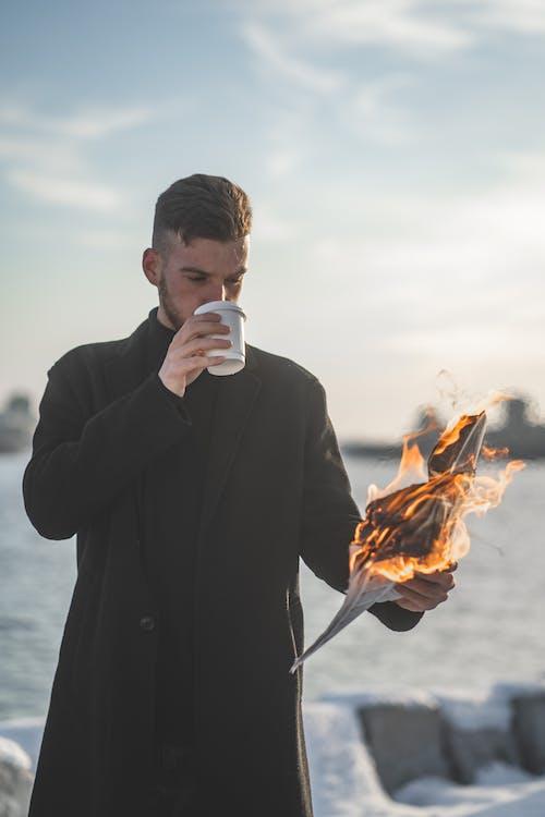 Man in Black Jacket Holding White Ceramic Mug With Fire