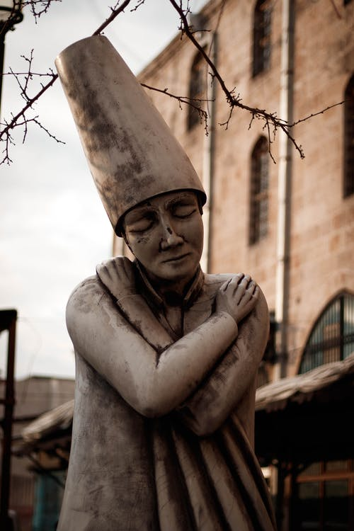 Stone monument of sorrowful female in tall hat hugging self located on street outside aged building on autumn day
