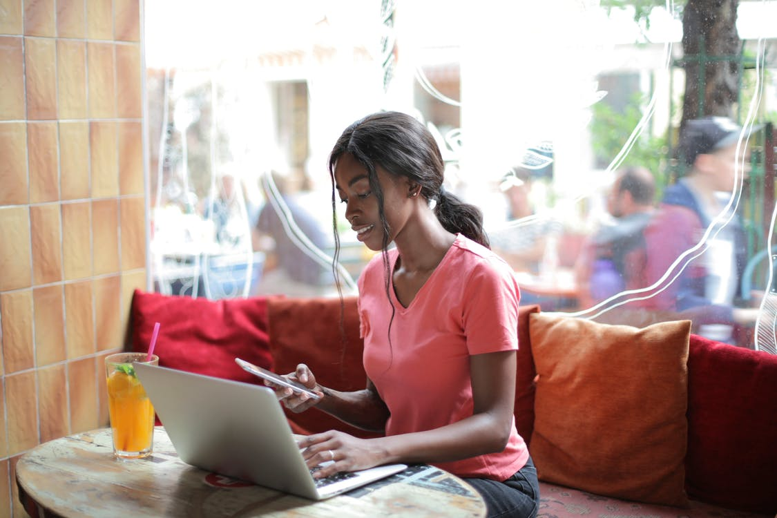 Woman in Pink Shirt Using Macbook and Smartphone