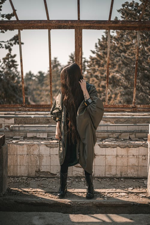 Full body of anonymous young woman with long dark hair covering face in stylish warm outfit standing in abandoned shabby building on sunny day