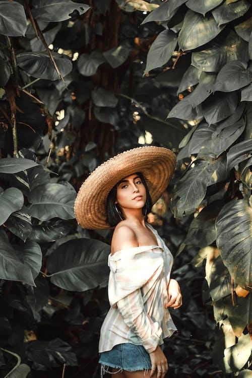 Yeşil Yaprakların Yanında Dururken Kahverengi Hasır şapka Giyen Kadın