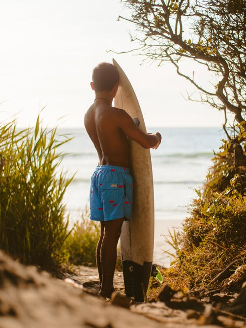 Topless Man in Blue Shorts While Holding White Surfboard
