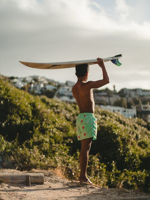 Topless Man in Green Shorts Holding Surfboard