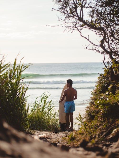 Man in Blue Denim Shorts Standing on Seashore