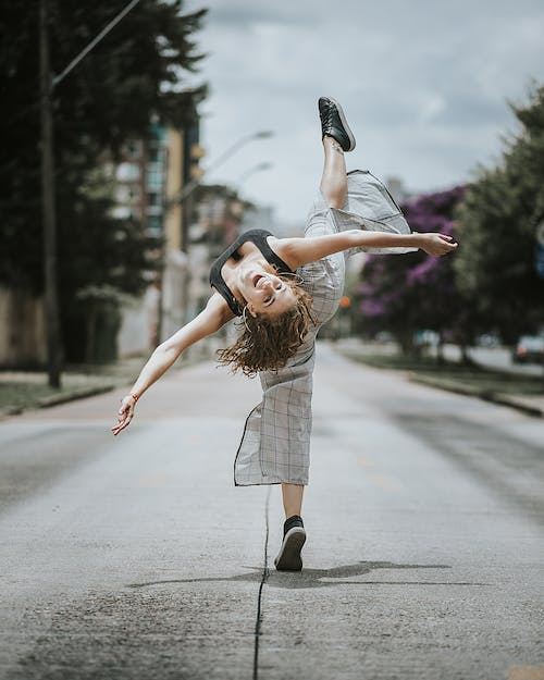 Happy young ballerina in casual wear dancing on street