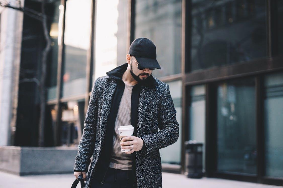 Stylish man with coffee to go walking on street