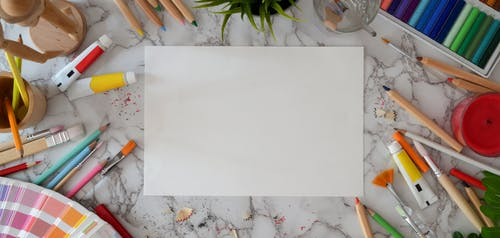 Top View Photo of White Bond Paper Near Coloring Materials
