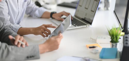Person in White Long Sleeve Shirt Using Silver Macbook