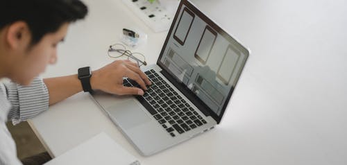 Person Using Macbook Air on White Table