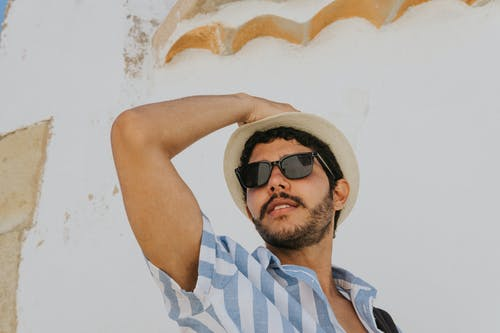 Man in Blue and White Stripe Polo Shirt Wearing Black Sunglasses and Brown Hat