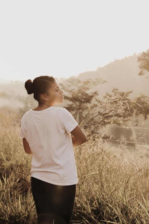 Photo of Woman Wearing White Shirt While Closing Her Eyes
