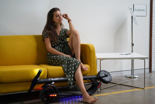 Základová fotografie zdarma na téma elektrický skútr, žena, žena sedí na gauči