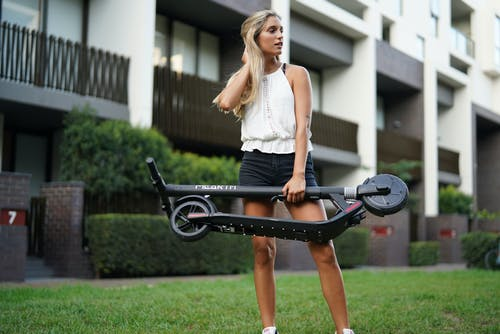 Shallow Focus Photo of Woman Holding Folded Electric Scooter