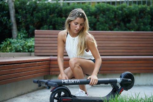 금발, 내려다 보는, 무릎 꿇고 있는, 스쿠터의 무료 스톡 사진