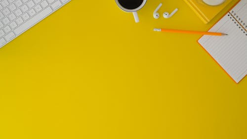 Top View Photo of Pencil, Earpods and Notepad on Yellow Surface