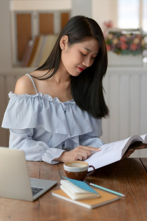 Woman in White Spaghetti Strap Shirt Reading Book