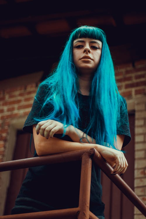 Woman With Blue Hair Leaning on Metal Railings