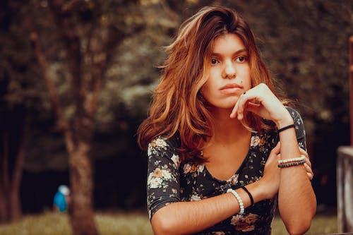 沉思的年轻女子在花园里做梦