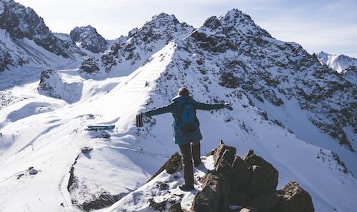 Mann In Der Blauen Jacke Und In Der Schwarzen Hose, Die Auf Schneebedecktem Berg Stehen