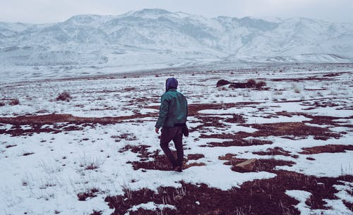 Person in Green Jacket Walking on Snow Covered Field