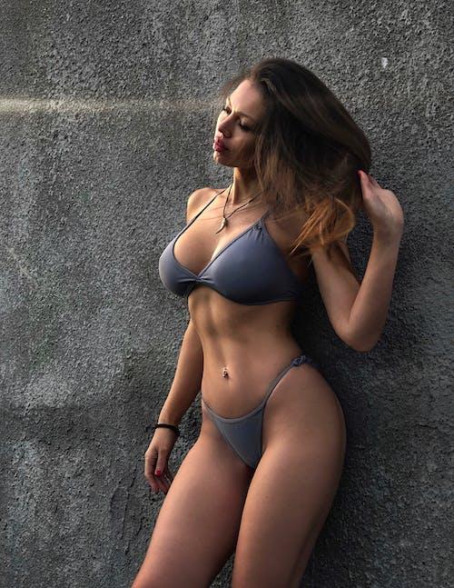 Бесплатное стоковое фото с бетонная стена, бикини, брюнетка, взмах волосами