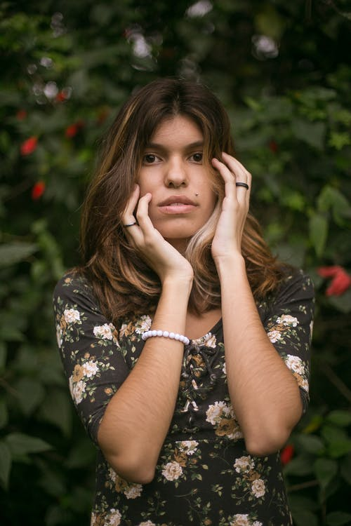 Woman in Floral Shirt Touching Her Face With Her Hands