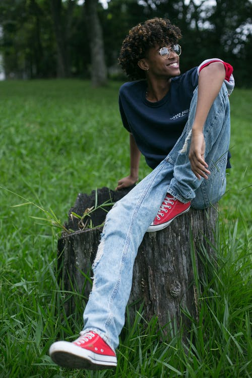 Man in Blue Crew Neck T-shirt and Blue Denim Jeans Sitting on Tree Log